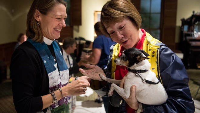 Rev. Monna Mayhall, left, blesses Moxie, held by owner Elizabeth Marshall, during the 22nd annual blessing of the animals at St. Paul's Episcopal Church in Franklin, Tenn., Sunday, Oct. 8, 2017.