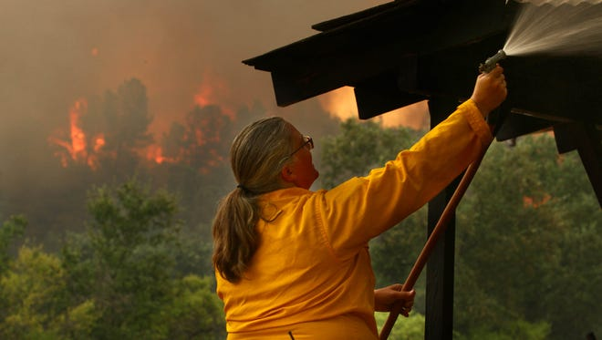 Lori Martin, superintendent of Shasta State Historical Park, sprays a roof to protect it from the flames of the Carr Fire. Cal Fire and fire departments in northern California get together to fight the Carr Fire on Thursday morning. The fire continued to move east from Shasta all the way to Iron Mountain Road. (Special to the Record Searchlight by photo by Hung T. Vu)