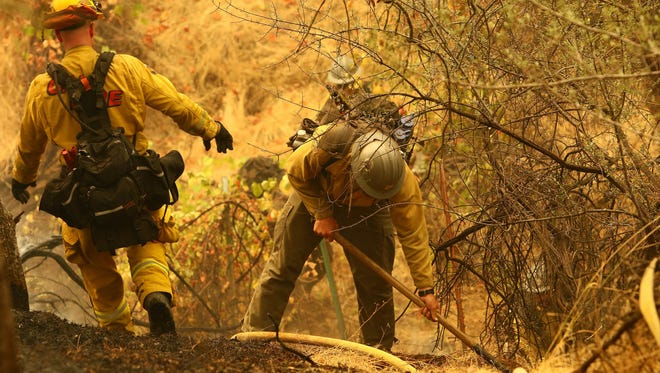 Hotshot firefighters walk on a field to build a defensive line in the Igo-Ono area. The Carr Fire spread to the southwest of Redding on Saturday morning. These images were captured along Placer Road and the Igo-Ono fire station.