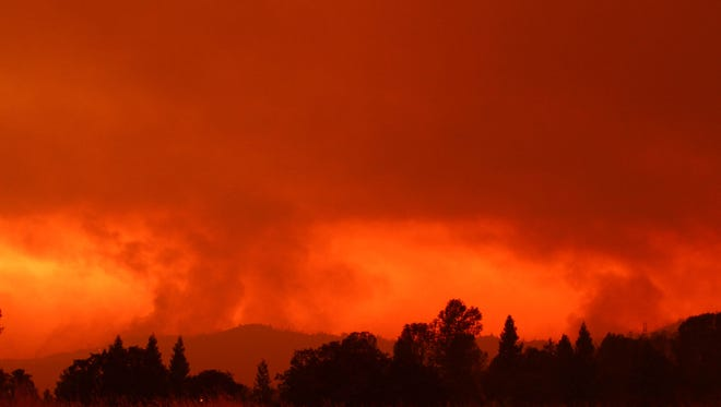 Friday afternoon, the Carr fire ignited again in the Redding, Calif. As the Sun set behind the mountains, smoke fills up the sky in the far distance.