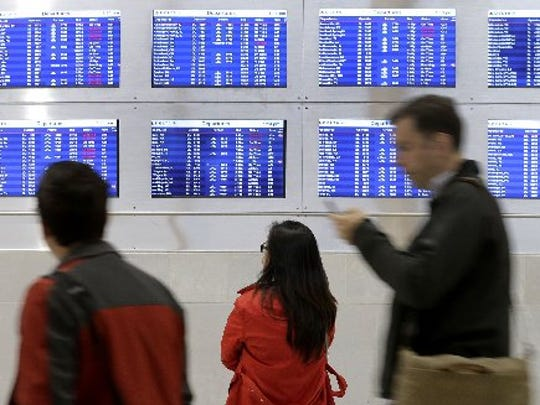 Travelers check flight arrivals and departures at Detroit