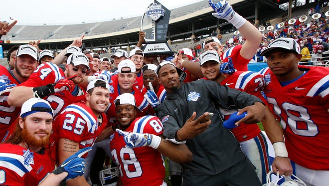 Louisiana Tech players hold up the Heart of Dallas Bowl trophy after beating Illinois in 2014. Dallas is one of several potential options for the Bulldogs this year.