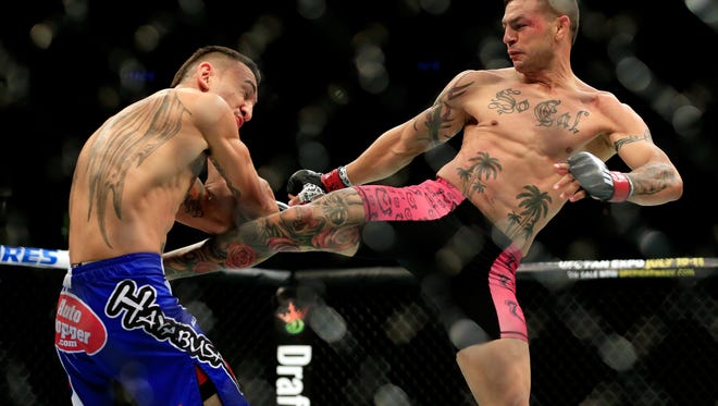 Cub Swanson kicks Max Holloway in their featherweight bout during the UFC Fight Night event at Prudential Center on April 18, 2015 in Newark, New Jersey.
