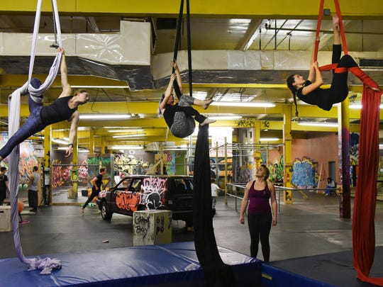 Instructor Anneliese LaTempa, standing, watches, from left, Holly Meyers, Heather Dozier and Elena Sacchi on the silks during a Level 2 Aerial Silks class at Urban Evolution Baltimore gym.