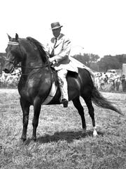 UVM Cantor, a 9-year-old stallion, with trainer Bob Baker up, at the Addison County field days on Hamilton Road, 1964.
