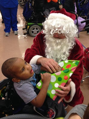 Santa helps Markus, a student at the Louisiana Special Education Center, open his gift at a party Monday.