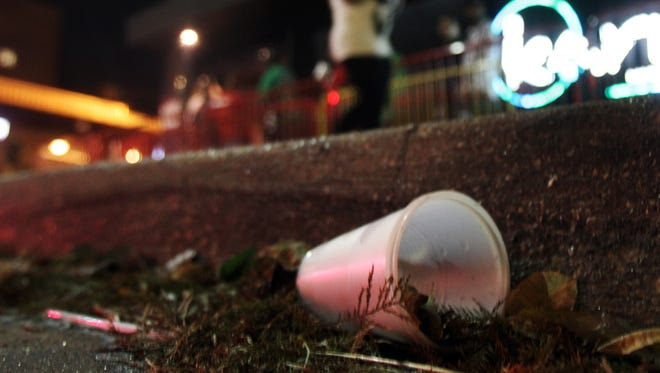 A discarded to-go cup is seen along the curb on Jefferson Street  in downtown Lafayette Thursday, November 4, 2010. (Leslie Westbrook/ lwestbrook@theadvertiser.com)