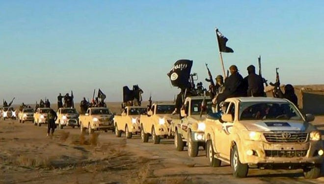 In this undated file photo released by a militant website, which has been verified and is consistent with other AP reporting, militants of the Islamic State group hold up their weapons and wave its flags on their vehicles in a convoy to Iraq, in Raqqa, Syria.