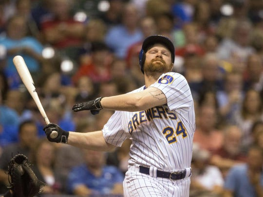 Milwaukee Brewers' Adam Lind swings at and misses a