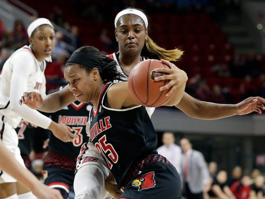 Louisville's Asia Durr (25) drives around North Carolina State's Kiara Leslie during the first half of an NCAA college basketball game in Raleigh, N.C., Sunday, Dec. 31, 2017. (AP Photo/Gerry Broome)