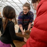 """Louisville Grows Garden Resource Coordinator Hadley Piper, center, explains to Addison Cordoba, 7, left, that by mixing different things together you can create a """"dirt recipe"""" for the seeds to grow in.  Feb. 26, 2015"""