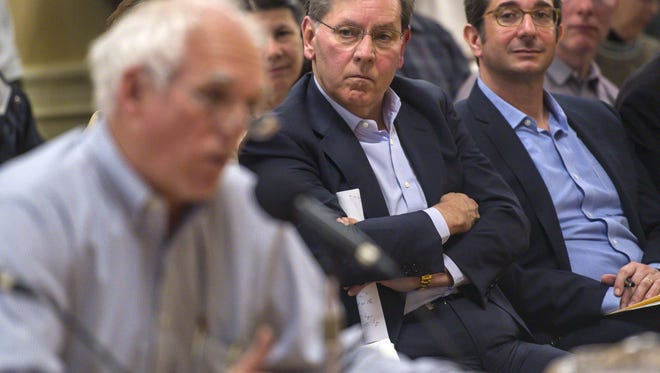 Developer Don Sinex, center, listens as Scott Baldwin, left, testifies during the public comment portion of a meeting where the Burlington City Council considered his redevelopment project proposed for the Burlington Town Center mall.