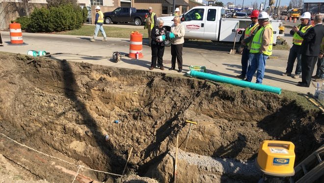 Eastpointe Mayor Suzanne Pixley, center left, and Macomb County Public Works Commissioner Candice Miller inspect the area  where a sanitary sewer line from an Eastpointe apartment complex was illegally connected to a relief drain that carries stormwater to Lake St. Clair.