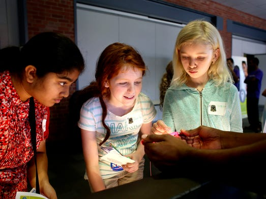 (left to right) Aditi Tarkar, Marilyn Buente and Virginia Sheldon learn about fiber optics from Kj Donar, right, during the fourth annual Youth Science Summit at GE's Appliance Park. June 14, 2014