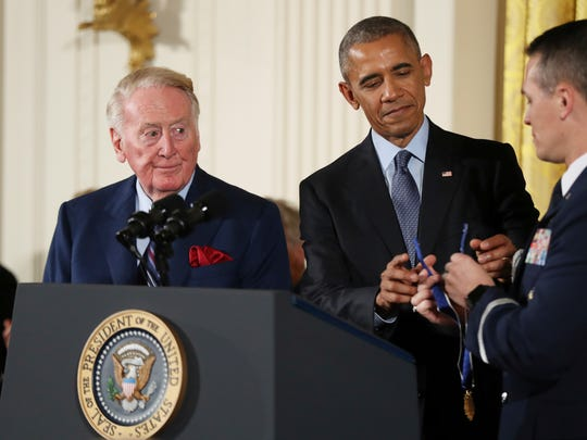 President Barack Obama presents the Presidential Medal of Freedom to sports broadcaster Vin Scully during a ceremony in the East Room of the White House, Tuesday, Obama recognized 21 Americans with the nation's highest civilian award.