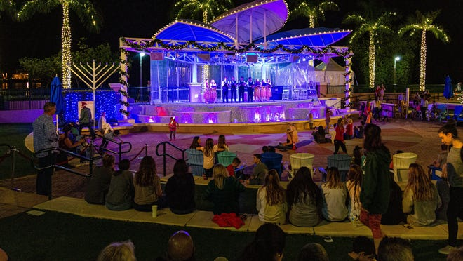 A crowd watches members of the Jupiter High School Choir perform holiday jingles at the Harbourside Place Amphitheater.  Harbourside Place in Jupiter held their annual Tree Lighting Ceremony on Saturday, November 23, 2019. Pianist John Tesh will perform at the amphitheater this weekend.