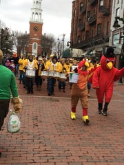 Accompanied by the UVM Pep Band, volunteers march in downtown Burlington on Saturday to benefit the Chittenden Emergency Food Shelf and the Burlington Sunrise Rotary.