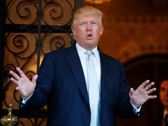 FILE - In this Wednesday, Dec. 28, 2016, file photo, President-elect Donald Trump speaks to reporters at Mar-a-Lago in Palm Beach, Fla.  Trump has singled out a number of companies individually, including General Motors Co., before and after winning the U.S. presidential election.