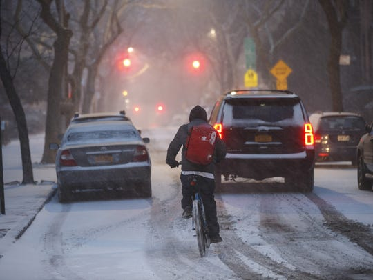 A man on a bicycle rides through the snow, Jan. 4,