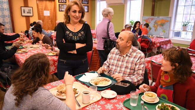 Najla Khoudur, center, a refugee from Syria, talking with her husband, Samer Albahri, and others in the Global Grace Cafe after a meeting of Interfaith-RISE at the Reformed Church of Highland Park in Highland Park on Wednesday.  Interfaith-RISE, a coalition of faith groups, resettles refugees in New Jersey.