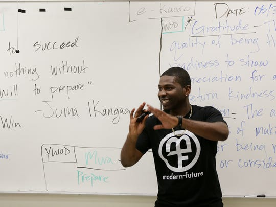 Eighth-grade teacher Olafemi Bankole Akintunde talks with his students during his Manhood Development Program at Westlake Middle School in Oakland, Calif. in June 2016.