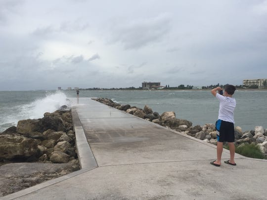 Joshua Sherman, 12, takes a photo of his mom, Stephanie, on the jetty south of the Fort Pierce Inlet before Hurricane Matthew arrives Thursday.