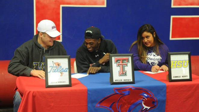Cooper's Myller Royals, center, has a laugh with Justin Wright, left, while Camille Scott looks on during their signing ceremony on Wednesday, Dec. 20, 2107 at Cooper High School. Royals signed to play football at Texas Tech, while Wright signed to play football at Tulsa. Scott will play softball at HSU.