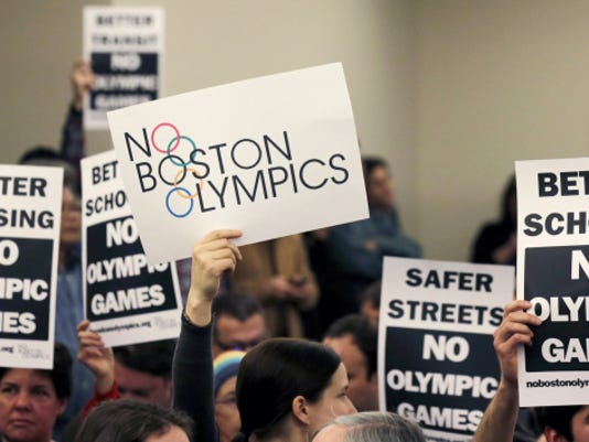 People hold up placards against the Olympic Games coming to Boston during the first public forum in February regarding the city's 2024 Olympic bid.