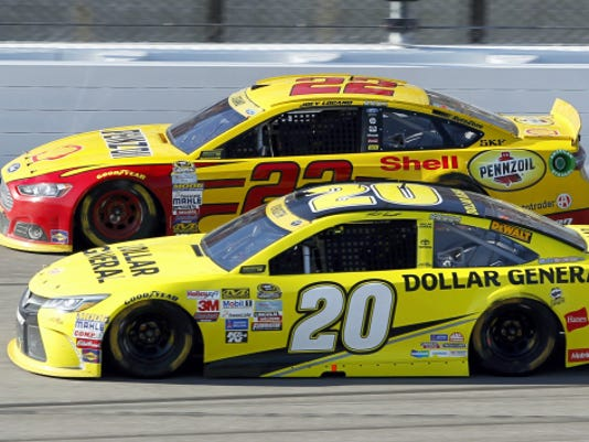 Sprint Cup Series driver Joey Logano (22) and Matt Kenseth (20) run side-by-side during a race Sunday at Kansas Speedway in Kansas City, Kan.