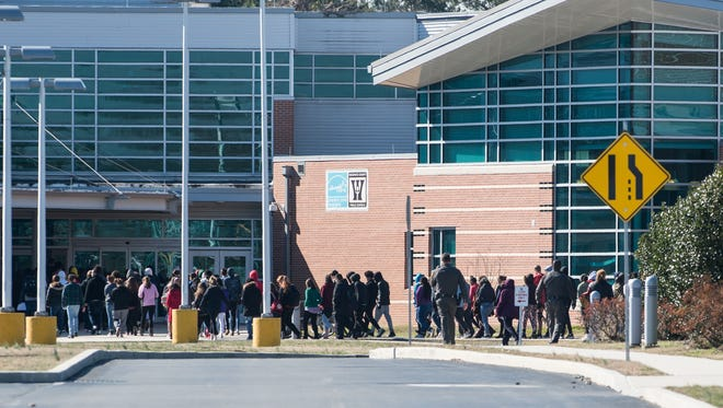 Students from James M. Bennett High School make their way indoors just after the National School Walkout on Wednesday, March 14, 2018.