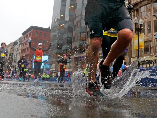 A runner splashes across the finish line of the 2018