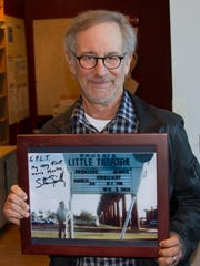 Steven Spielberg, holding a picture of his first movie premiere at Phoenix Theatre when he was in high school.