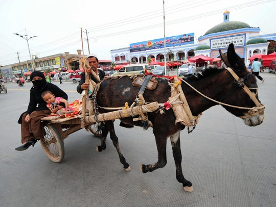 A woman and child get a ride on a donkey cart passing the Sunday Bazaar in Kashgar in northwest China's Xinjiang Uighur Autonomous Region. Once the sole outpost of civilization leading from the vast deserts and mountain ranges of Central Asia but no longer so remote, Kashgar has been a Silk Road trading center for over two millennia retaining its fascinating ethnic mix of Uighurs, Tajiks, Kyrgyz, Uzbeks and Han Chinese.