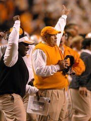 Tennessee head coach Philip Fulmer signals a recovered fumble in the fourth quarter against South Carolina on Saturday at Neyland Stadium. The Vols survived a second half defensive collapse to win 27-24 in overtime, improving to 5-3 for the season. At left is assistant Gerald Harrison.  Photo by Michael Patrick, Knoxville News Sentinel