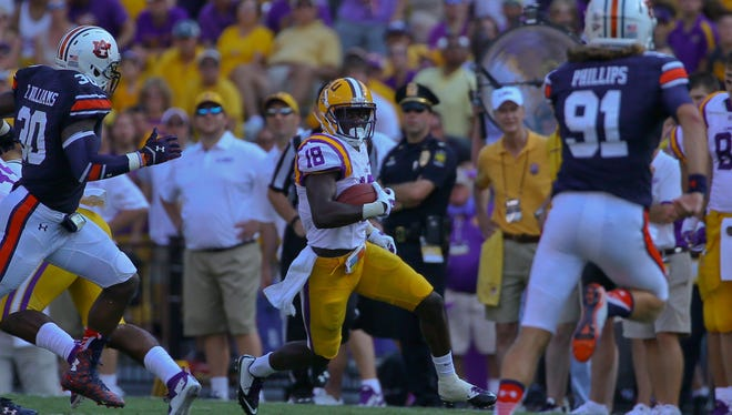 LSU Tigers cornerback Tre'Davious White (18) runs back an interception against the Auburn Tigers during the second half of a game at Tiger Stadium. LSU defeated Auburn 45-21.