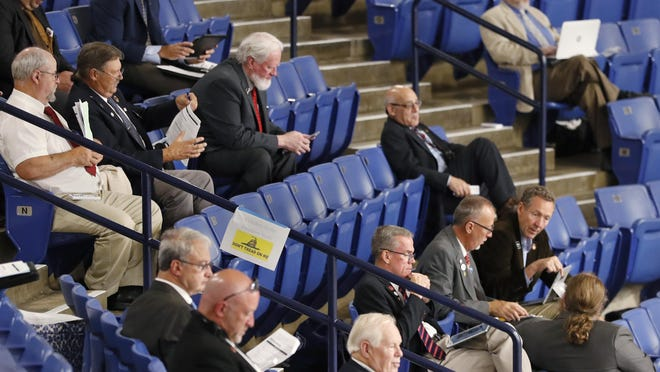 """N.H. House of Representative members, who choose not wear a protective masks, sit in the """"freedom seats"""" of the stands during a legislative session overlooking the drained ice hockey rink at the University of New Hampshire on Tuesday, June 30, 2020, in Durham. Lawmakers were required to wear either face masks or plastic face shields on the floor, though there were separate sections in the stands for those who couldn't do so for medical reasons, and another section for about two dozen lawmakers who refused."""