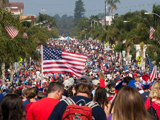 An American flag is hoisted over the crowd marching