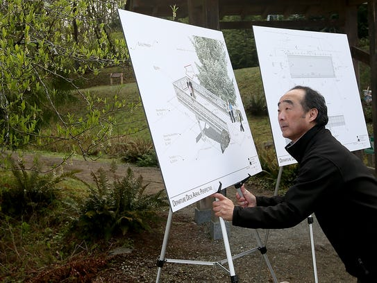 Clarence Moriwaki, president of the Bainbridge Island Japanese American community, with renderings of what the departure deck will look like.
