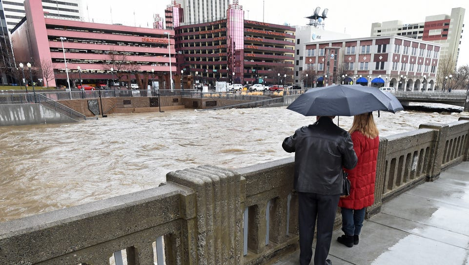 File photo: A couple watches the river flow in downtown