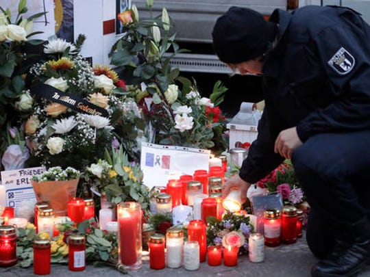 FILE - In this Dec. 20, 2016 file photo a police officer lights a candle in Berlin, Germany the day after a truck ran into a crowded Christmas market nearby. German prosecutors say they've detained a Tunisian man they think may have been involved in last week's truck attack on a Christmas market in Berlin. Federal prosecutors said Wednesday Dec. 28, 2016  the 40-year-old was detained during a search of his home and business.