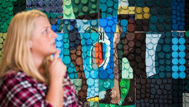 Ivy Tech student Andrea Manning checks out art from other students in their recycled pill bottle collage Friday. The art exhibit, which is intended to depict the effects of non-compliance to proper prescription drug use,  is on display in the South Tower atrium of IU Health Ball Memorial Hospital.