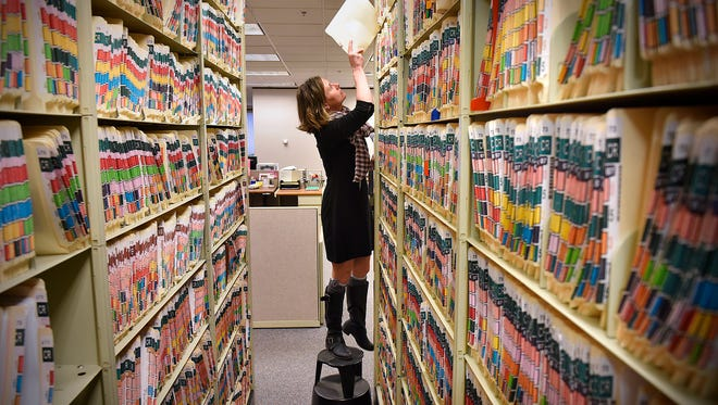 Stearns County Court Administration Criminal Division Team Leader Lisa Braaten removes one of the original files stored at court offices Thursday, Dec. 3 in St. Cloud.