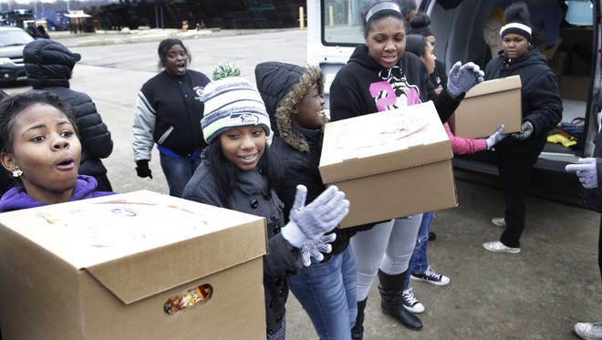 Torrianna Bradley, 17, a senior at Cody high school, left, gets help from her fellow classmates as they loaded boxes at the UAW-Ford Brownstown Packaging Depot into a van going to Miracle Tabernacle in Detroit. Students from six metro Detroit schools volunteer to load up nearly 16,700 food boxes that included a turkey and trimmings as part of the UAW-Ford Holiday Box of Love Project last year.