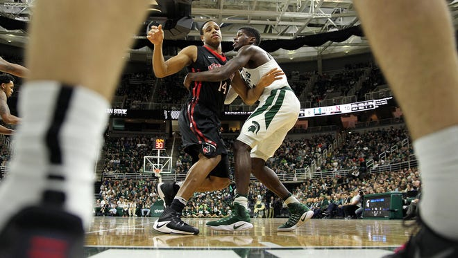 Michigan State guard Eron Harris (14) defends Northeastern forward Maxime Boursiquot (14) during the first half Sunday at Breslin Center.