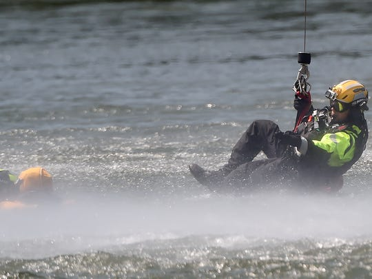 """A member of the Pennsylvania Helicopter Aquatic Rescue Team  is lowered into the water of Lake Williams as he """"rescues"""" a member of the Pennsylvania Fish and Boat Commission. Both teams were participating in a water rescue simulation at the lake which involved using both Blackhawk and Chinook helicopters on Saturday, August 20, 2016."""