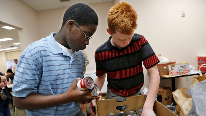 Victor Oliver of the Dunkers, a local AAU eighth grade basketball team, and Tyler Smith sort canned goods Wednesday, December 23, 2015, at Lafayette Transitional Housing Food Pantry, 615 N. 18th Street, Suite 102 in Lafayette. Many of the items will be featured in a Christmas meal the team is preparing and serving from 5 to 6 p.m. Christmas Eve at Lafayette Transitional Housing. Each member of the team will bring two pan dishes to the meal. Additionally, Dunkers coach John Smith and his wife, Kelly, are cooking three turkeys for the meal. Each member of the team will be working on the serving line to help feed those in need.