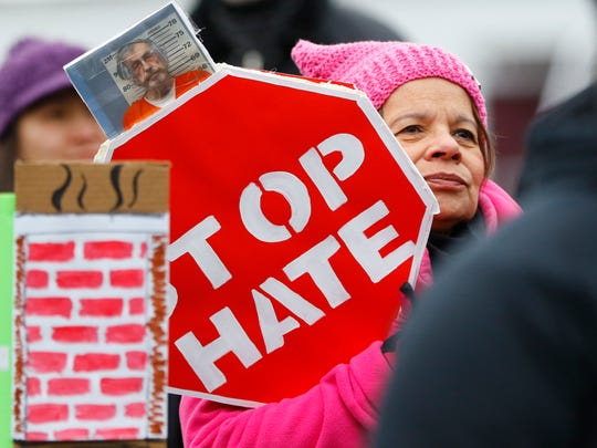 Margarita Renteria, of Stevens Point, holds up a sign