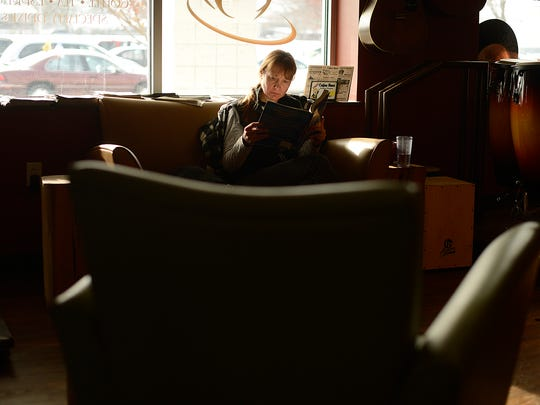 Aileen Riggins of Appleton reads inside Harmony Cafe in Green Bay on Wednesday. Riggins, who is a student at NWTC, usually spends time at the cafe after her classes.