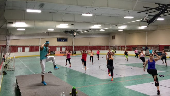 Instructor Gil Gonzalez leads his Zumba class at Fort Myers Skadium.