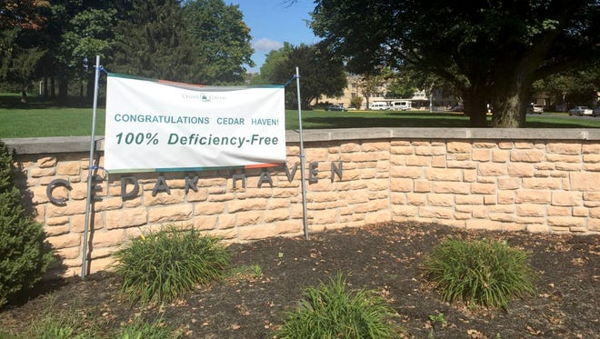 A sign celebrating its 100 percent deficiency-free rating hangs at the entrance to Cedar Haven nursing home in South Lebanon Township, where employees are in contract negotiations with the owner. A strike called for Oct. 15 has been put on hold.